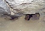 Przejście przez zawał - w tym miejscu strop się zapadł i mamy tylko tyle miejsca na prześlizgnięcie się dalej - to ta dziura przy mej głowie. Zawał utrudnia również przewietrzanie dalszych partii sztolni. Pod tym piaskiem jest lita skała więc przekopać się łatwo nie da