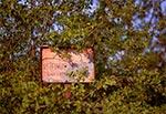 Stara tabliczka rezerwatu Susła - Hubale pod Zamościem. W środku widoczny ślad po kuli.